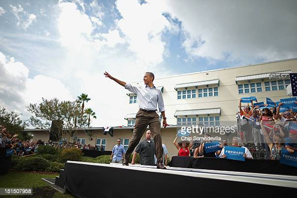 S President Barack Obama waves to supporters as he takes the stage during a campaign on the campus of St Petersburg College September 8 2012 in St...