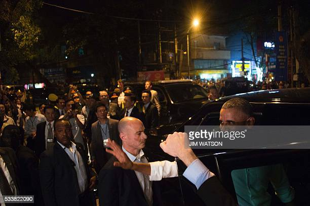 US President Barack Obama waves to the crowd as he departs after eating dinner at Bun cha Huong Lien with CNN's Anthony Bourdain in Hanoi late on May...