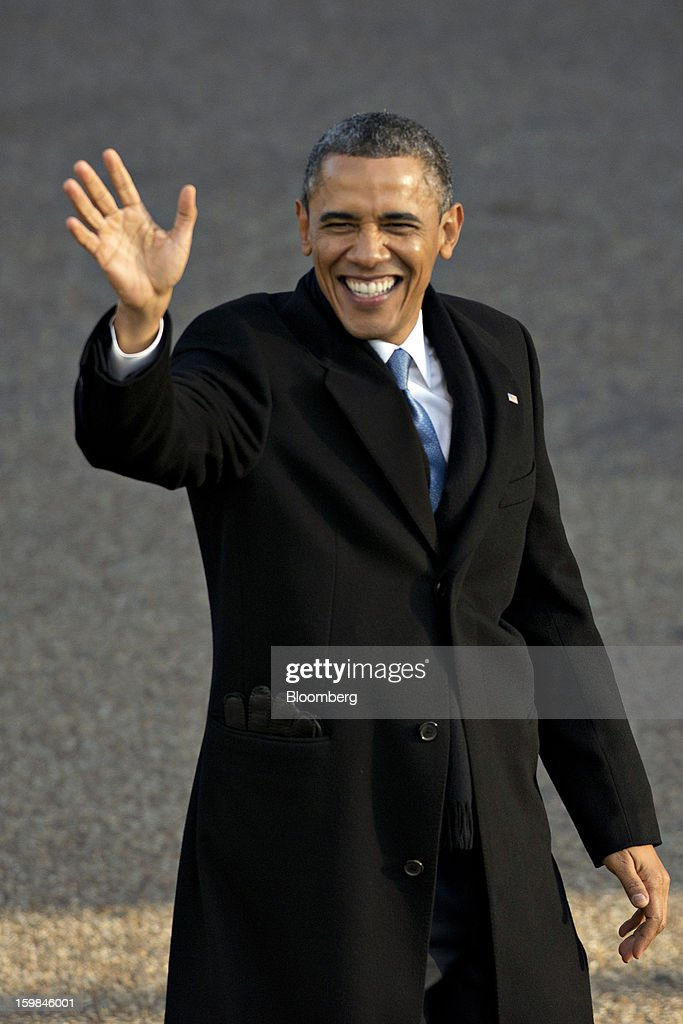 U.S. President Barack Obama waves to the crowd as he walks along the parade route during the presidential inauguration in Washington, D.C., U.S., on Monday, Jan. 21, 2013. A crowd estimated by police to be as large as 700,000, including warmly dressed women with American flags stuck in their hair, a smattering of celebrities and many Republicans, gathered today to witness President Barack Obama take his second oath of office on the steps of the U.S. Capitol. Photographer: Daniel Acker/Bloomberg via Getty Images