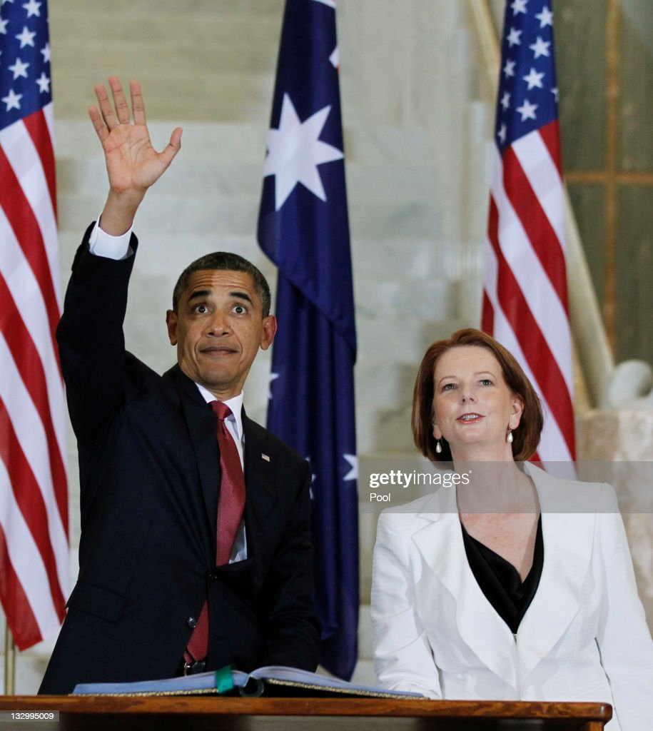 U.S. President Barack Obama waves to the public inside the Parliament House as Australian Prime Minister Julia Gillard looks on, the Parliament House on the first day of his 2-day visit to Australia, on November 16, 2011 in Canberra, Australia. The President will today receive a Cermeonial Welcome, attend a bi-lateral meeting and hold a joint media conference with Julia Gillard, and attend a Parliamentary Dinner this evening, before addressing Parliament and heading to Darwin tomorrow.