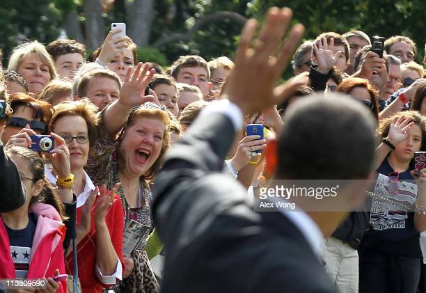 S President Barack Obama waves to visitors as he walks towards the Marine One for a departure on the South Lawn of the White House May 6 2011 in...