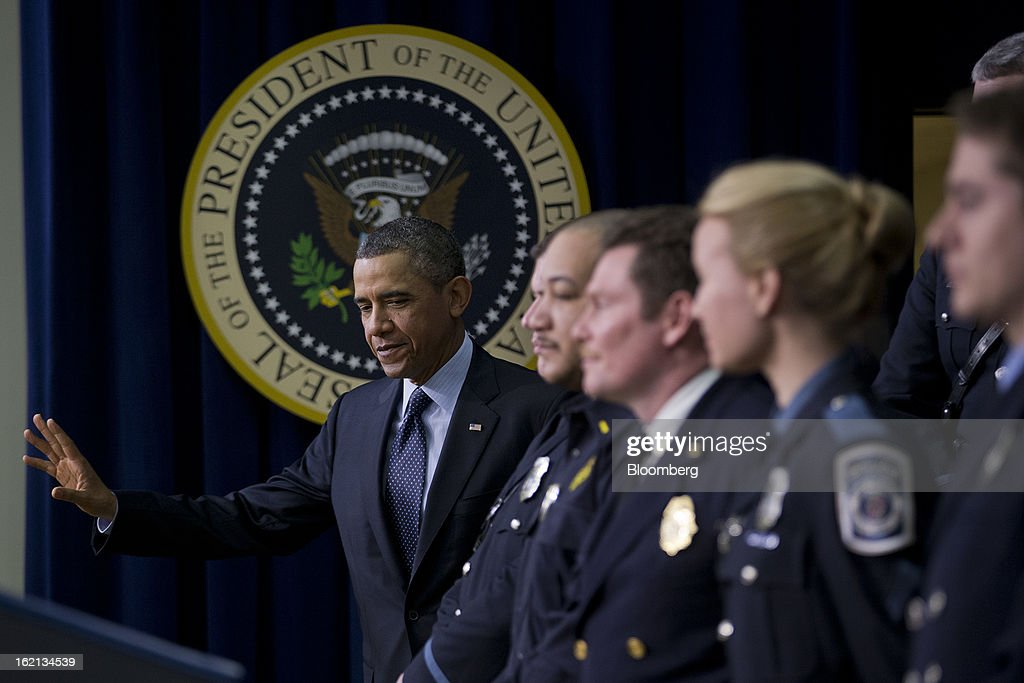 U.S. President Barack Obama waves while arriving to speak next to emergency responders, right, in the South Court Auditorium of the Eisenhower Executive Building next to the White House in Washington, D.C., U.S., on Tuesday, Feb. 19, 2013. Obama stepped up pressure on Congress to avert 'brutal' automatic $1.2 trillion in budget cuts set to kick in March 1, saying it would harm the economy and curtail vital services. Photographer: Andrew Harrer/Bloomberg via Getty Images