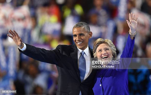 US President Barack Obama waves with US Presidential nominee Hillary Clinton during the third night of the Democratic National Convention at the...