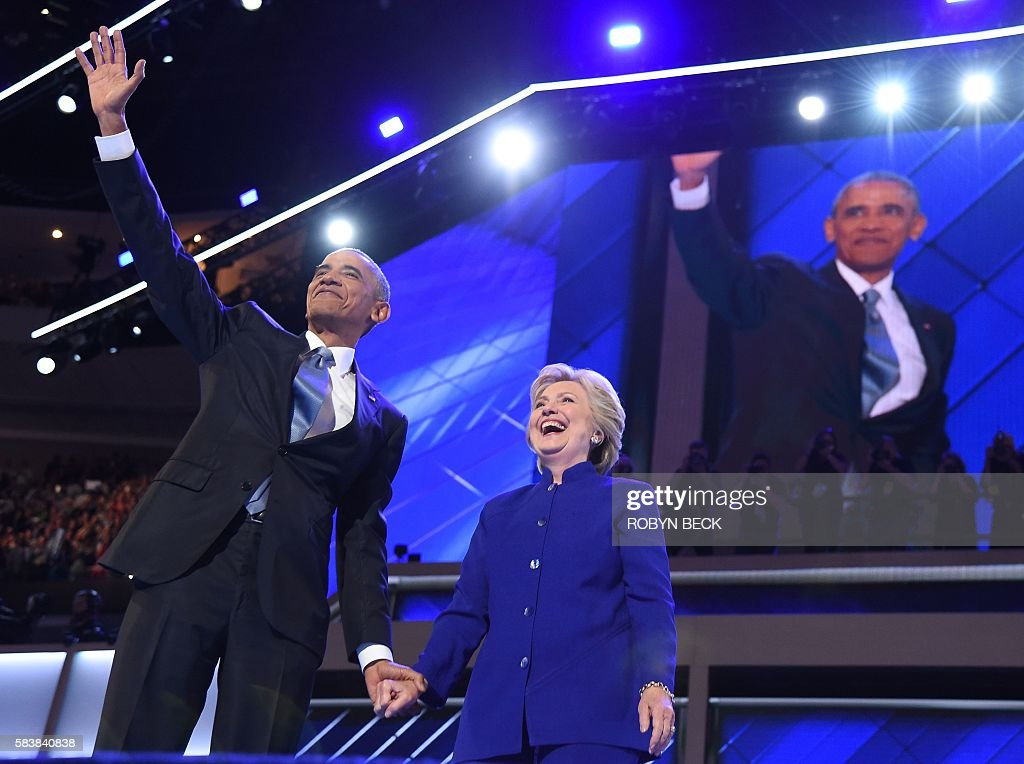 President Barack Obama (L) waves with US Presidential nominee Hillary Clinton during the third night of the Democratic National Convention at the Wells Fargo Center in Philadelphia, Pennsylvania, July 27, 2016. / AFP / Robyn BECK