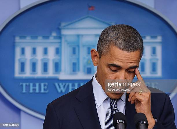 US President Barack Obama wipes a tear from his eye as he speaks during a previously unannounced appearance in the Brady Briefing Room of the White...