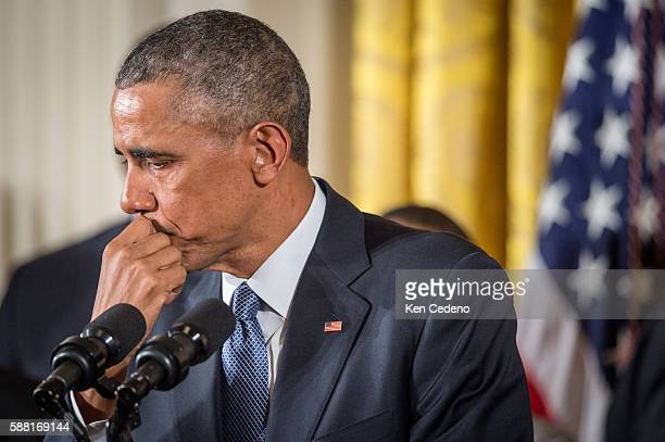 US President Barack Obama wipes away tears as he talks about needless shootings at Sandy Hook Elementary school during a press briefing in the East...