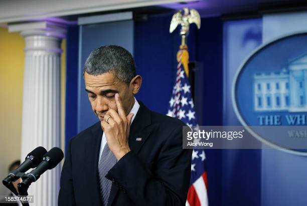 President Barack Obama wipes tears as he makes a statement in response to the elementary school shooting in Connecticut December 14, 2012 at the...