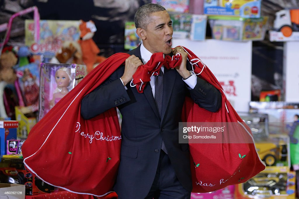 U.S. President Barack Obama, with bags slung over his shoulders, delivers toys and gifts donated by Executive Office of the President staff to the Marine Corps Reserve Toys for Tots Program at Joint Base Anacostia-Bolling December 10, 2014 in Washington, DC. For 67 years the Toys for Tots program has worked with local communities to collect and distribute toys and gifts for less fortunate children throughout the United States.