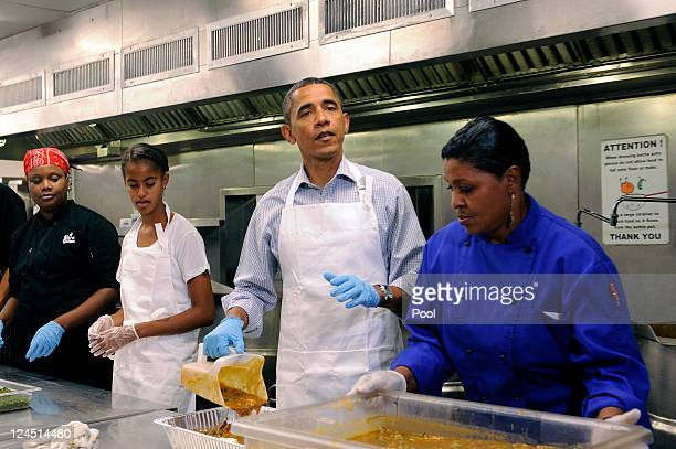 US President Barack Obama with daughter Malia Obama and from left Jamillah Linkins and Marianne Ali participate in a service project to commemorate...