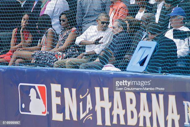 S President Barack Obama with daughters Malia and Sasha Obama and first lady Michelle Obama talks to Cuban President Raul Castro during a moment of...