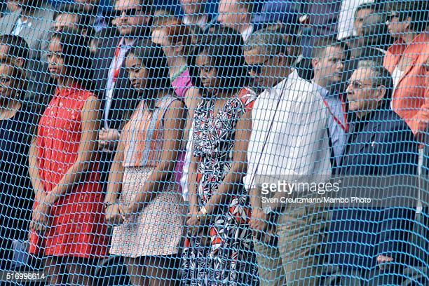 S President Barack Obama with daughters Malia Obama Sasha Obama and first lady Michelle Obama stands next to Cuban President Raul Castro as they bow...