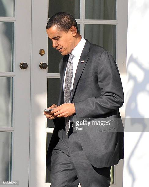 S President Barack Obama works on his Blackberry on his belt as he returns to the Oval Office at the White House January 29 2009 in Washington DC...