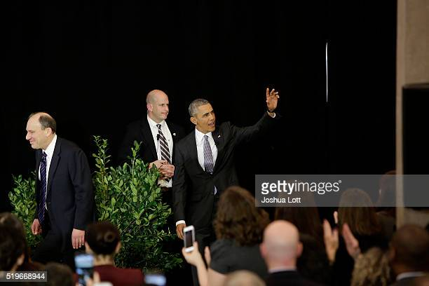 President Barack Obamaright waves to attendees as he arrives at the University of Chicago Law School with Law Professor David Strauss left on April 7...