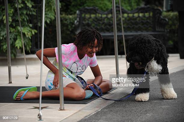 US President Barack Obama's daughter Malia plays with the family's pet dog Bo as she waits for the Marine One presidential helicopter to land on the...