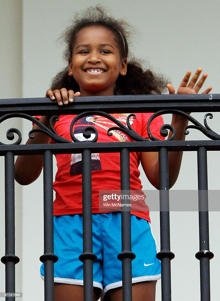 U.S. President Barack Obama's daughter Sasha waves to him from the Truman Balcony after he arrived on the south lawn of the White House via Marine One May 14, 2009 in Washington, DC. Obama was returning from a trip to Arizona and New Mexico.