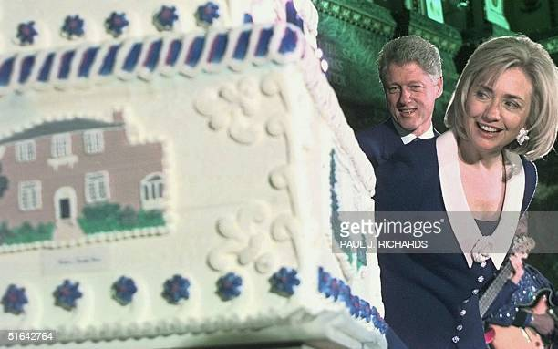 President Bill Clinton and First Lady Hillary Clinton look at at 300 pound birthday cake presented for her 50th birthday celebration 27 October at...