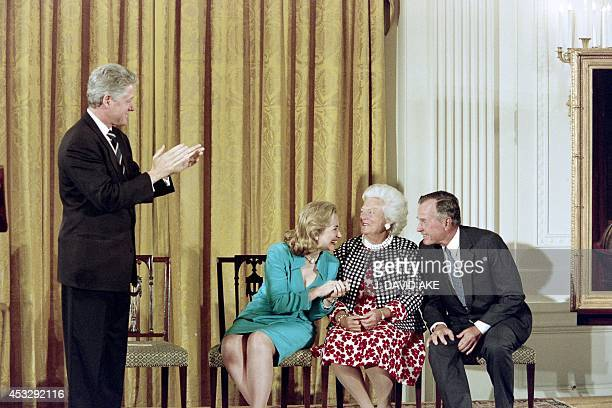US President Bill Clinton and First Lady Hillary Clinton share a light moment with Barbara Bush and former President George Bush during the unveiling...