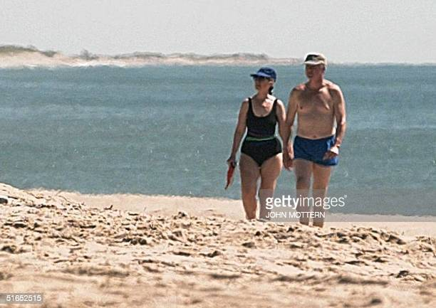 US President Bill Clinton and First Lady Hillary Clinton walk the beach on Martha's Vineyard MA where the first family is vacationing 26 August AFP...