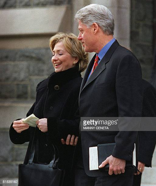 President Bill Clinton and First Lady Hillary Rodham Clinton talk as they walk out of the Foundry Methodist Church 19 December 1999 in Washington DC...