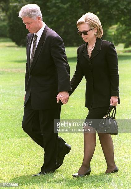 President Bill Clinton and First Lady Hillary Rodham Clinton walk handinhand across the lawn of the White House 13 August in Washington DC after...
