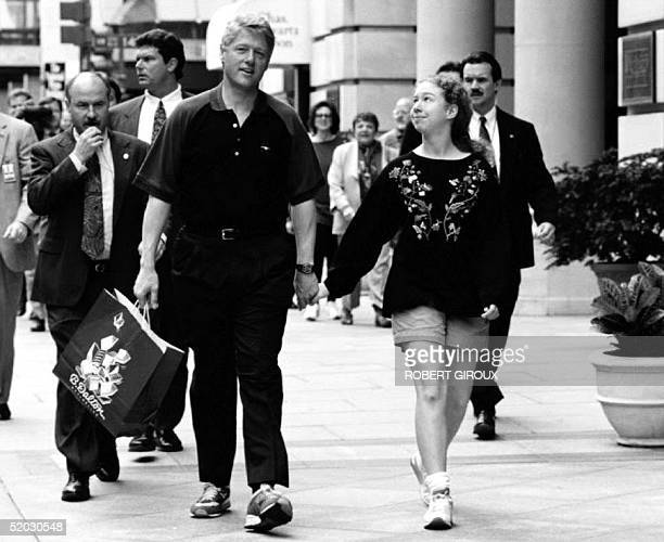S President Bill Clinton and his daughter Chelsea are accompanied by security personnel as they walk back to the White House 23 May 1993 after...