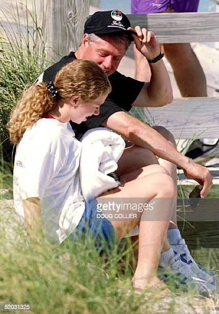 S President Bill Clinton and his daughter Chelsea talk 05 September 1993 while sitting on the beach near their hotel The Clintons are in South...