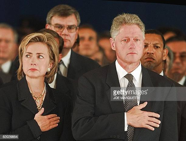 President Bill Clinton and his wife Hillary Rodham Clinton hold their hands over their hearts 13 August at Andrews Air Force Base during a memorial...