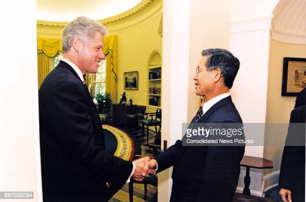 US President Bill Clinton and Peruvian President Alberto Fujimori shake hands in the White House's Oval Office Washington DC May 21 1996