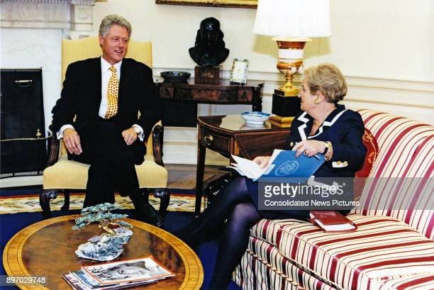 US President Bill Clinton and Secretary of State Madeleine Albright talk together in the White House's Oval Office Washington DC September 8 1997