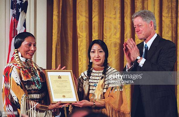 President Bill Clinton applauds after handing the plaque naming Native American Sacagawea honorary scout of the Corps of Discovery to Rose Anne...