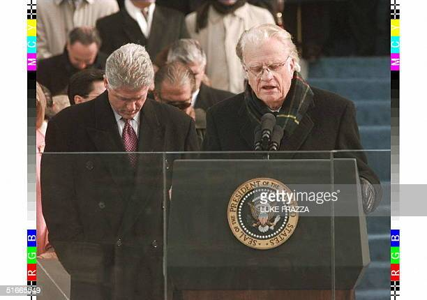 President Bill Clinton bows his head as Reverend Billy Graham gives the invocation at the beginning of the inaugural ceremony 20 January on Capitol...