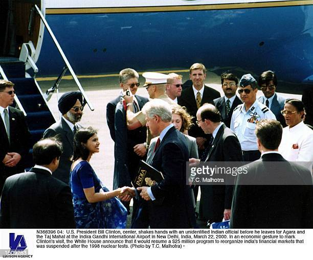 S President Bill Clinton center shakes hands with an unidentified Indian official before he leaves for Agara and the Taj Mahal at the Indira Gandhi...