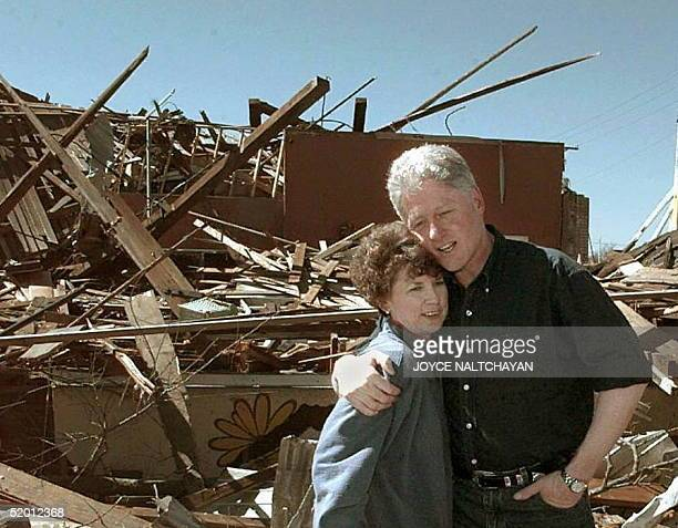 President Bill Clinton comforts Judy Sligh during a tour of damage in Arkadelphia Arkansas 04 March after a series of tornados ruined hundreds of...