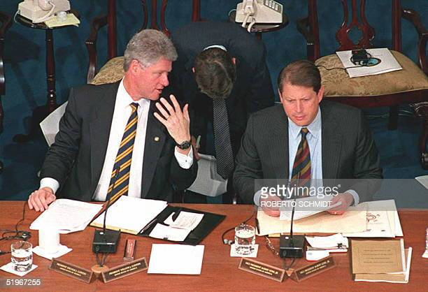 President Bill Clinton confers with an unidentified aide at the beginning of the first working session of the Summit of the Americas 10 December 1994...