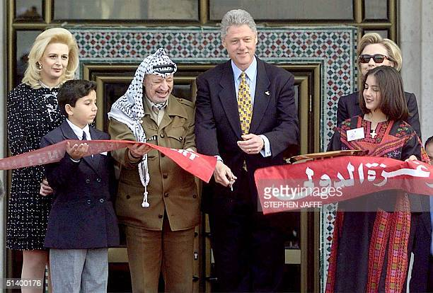 President Bill Clinton cuts the ribbon at Gaza international airport 14 December in Rafah in the Gaza Strip with Palestinian leader Yasser Arafat,...