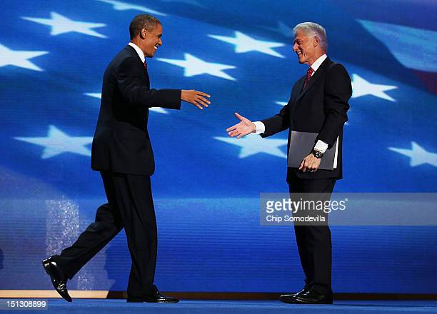 S President Bill Clinton greets Democratic presidential candidate US President Barack Obama on stage during day two of the Democratic National...