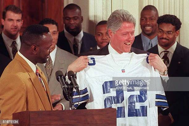 President Bill Clinton holds a Dallas Cowboys jersey presented to him by running back Emmitt Smith bearing Smith's number during a ceremony 13...