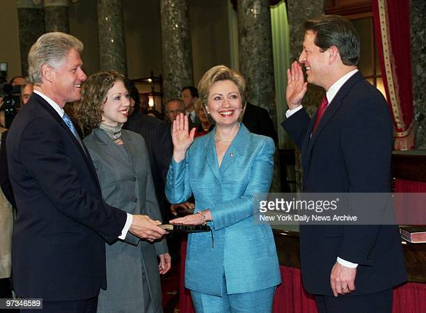 President Bill Clinton holds bible and daughter Chelsea looks on as Hillary Rodham Clinton and Vice President Al Gore go through a recreation of her...