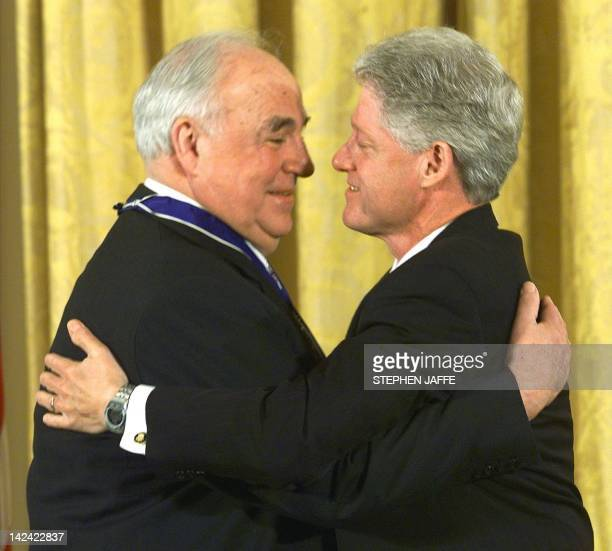 US President Bill Clinton hugs former German Chancellor Helmut Kohl after awarding the Medal of Freedom award to Kohl in the East Room of the White...