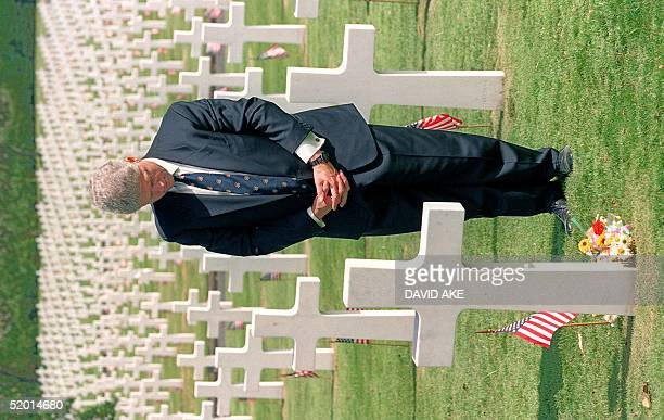 President Bill Clinton in a picture taken 13 November 1994 in Manila prays over the grave of Private First Class William Thomas of Wynne Arkansas at...