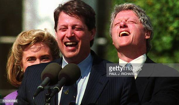 President Bill Clinton laughs 23 April 1993 as Vice President Al Gore jokes with White House volunteers attending a reception in their honor. Peeking...