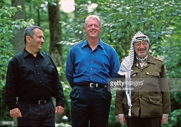 President Bill Clinton laughs with Israeli Prime Minister Ehud Barak and Palestinian President Yasser Arafat July 11, 2000 at Camp David during peace...