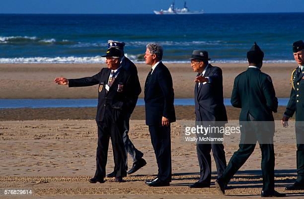 President Bill Clinton listens to DDay veterans at Omaha Beach on the 50th anniversary of the Normandy invasion Two active Army members stand behind...