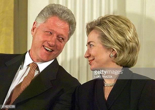 President Bill Clinton looks at First Lady Hillary Clinton 17 February in Washington as US Senator Chuck Robb, D-VA, makes a joke about Mrs....
