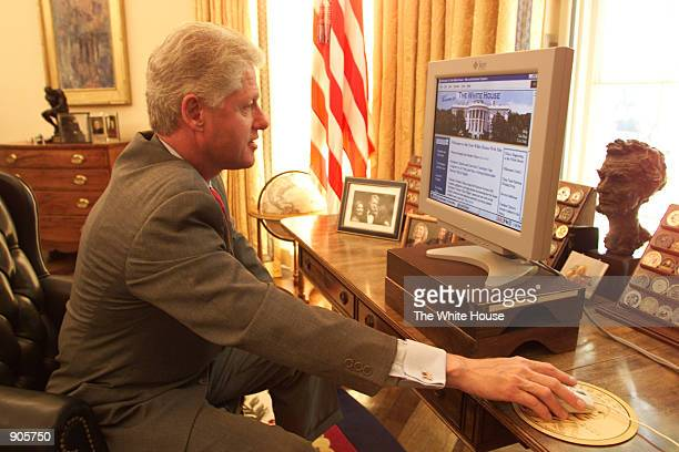 President Bill Clinton looks at the new White House web site in Oval office July 8 2000