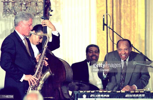 President Bill Clinton plays the saxophone as jazz vibraphonist Lionel Hampton gives a thumbs up during a birthday celebration July 24 1998 marking...