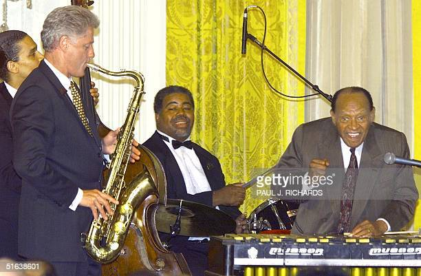 President Bill Clinton plays the saxophone next to jazz great Lionel Hampton during a 90th birthday celebration of Hampton in the East Room of the...