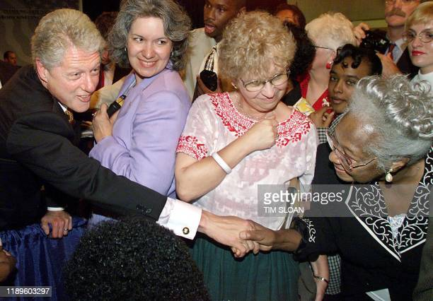 US President Bill Clinton reaches out to Medicare recipient Frankie Watts after he participated in a Medicare forum at the Lansing Community College...
