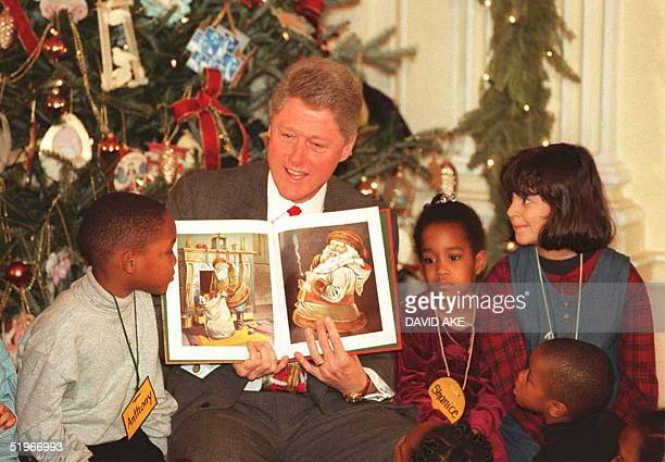 President Bill Clinton reads Twas the Night Before Christmas during a party in the White House State Dining Room 22 December 1994 The party was held...