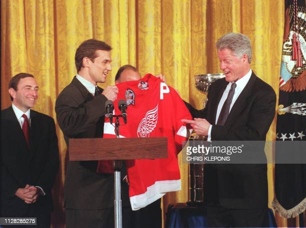 US President Bill Clinton receives an ice hockey sweater from Steve Yzerman captain of the Stanley Cup winning Detroit Red Wings 28 January at a...